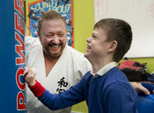 An Ikkaido coach with a young person with a disability laughing with joy and striking a punchbag.